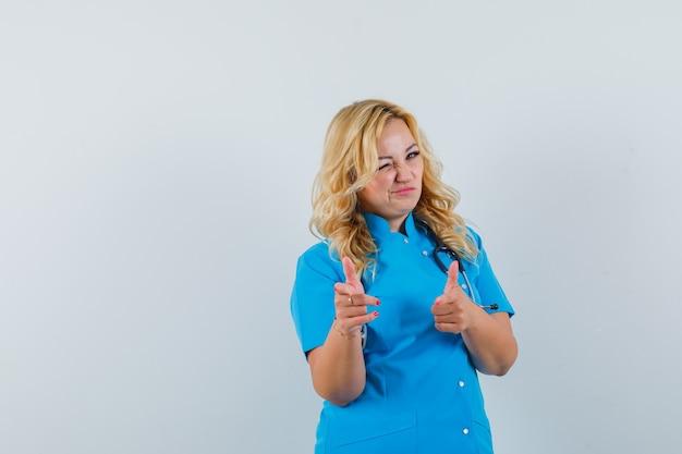 Ärztin, die auf kamera zeigt, während sie in der blauen uniform zwinkert und sicher aussieht. platz für text Kostenlose Fotos