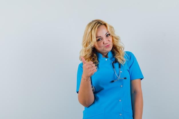 Ärztin, die daumen oben in der blauen uniform zeigt und optimistischen raum für text sucht Kostenlose Fotos