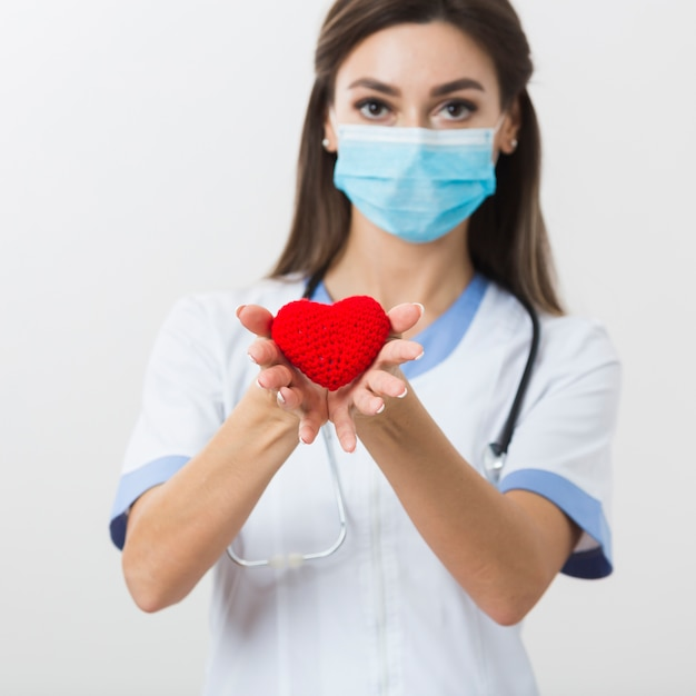 Ärztin, die ein plüschherz anbietet Premium Fotos