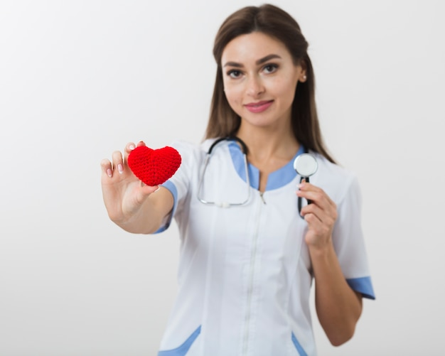 Ärztin, die ein plüschherz und ein stethoskop hält Kostenlose Fotos