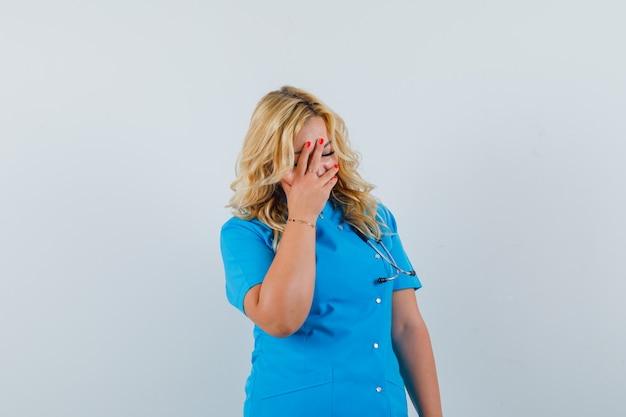 Ärztin, die hand auf ihrem gesicht in der blauen uniform hält und gelangweilt aussieht Kostenlose Fotos