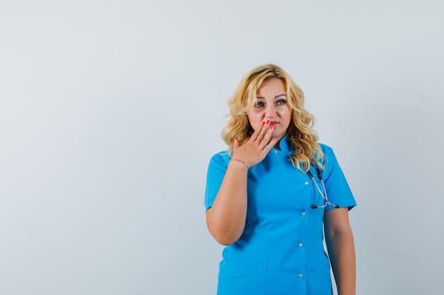 Ärztin, die hand auf ihrer lippe in der blauen uniform hält und verärgert aussieht. platz für text Kostenlose Fotos