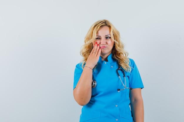 Ärztin, die hand auf ihrer wange hält, während sie in blauer uniform zur seite schaut und unzufrieden aussieht. platz für text Kostenlose Fotos