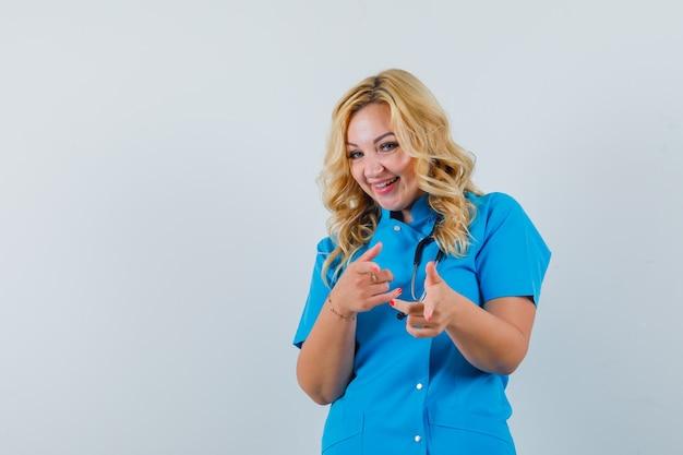 Ärztin, die in blauer uniform auf kamera zeigt und amüsiert aussieht. platz für text Kostenlose Fotos