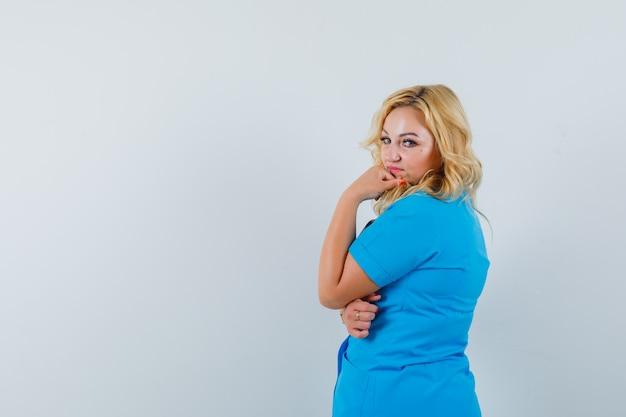 Ärztin, die in blauer uniform beiseite schaut und nachdenklich aussieht. . platz für text Kostenlose Fotos