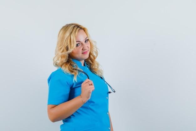 Ärztin, die in blauer uniform beiseite schaut und niedlich schaut. . platz für text Kostenlose Fotos