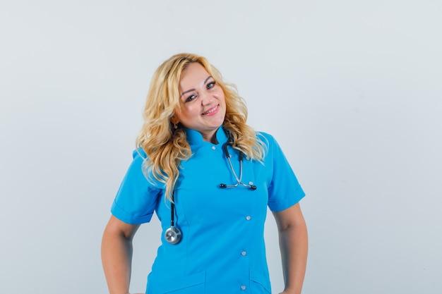 Ärztin, die in der blauen uniform lächelt und fröhlich schaut Kostenlose Fotos