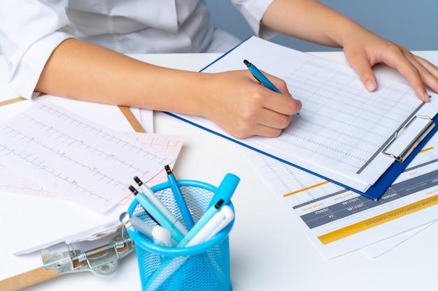 Ärztin, die kenntnisse über klemmbrett beim sitzen an ihrem tisch im büro nimmt Premium Fotos