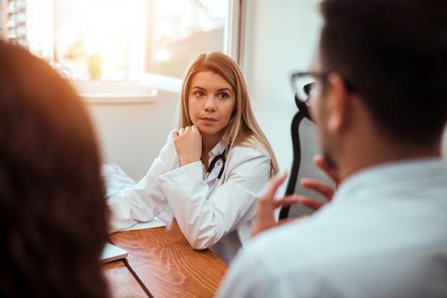 Ärztin, die mit jungen paaren im raum des doktors sich berät. Premium Fotos