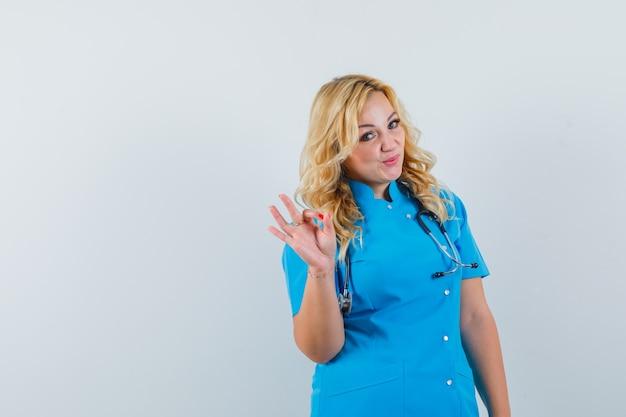 Ärztin, die ok geste in der blauen uniform zeigt und erfreuten raum für text sucht Kostenlose Fotos