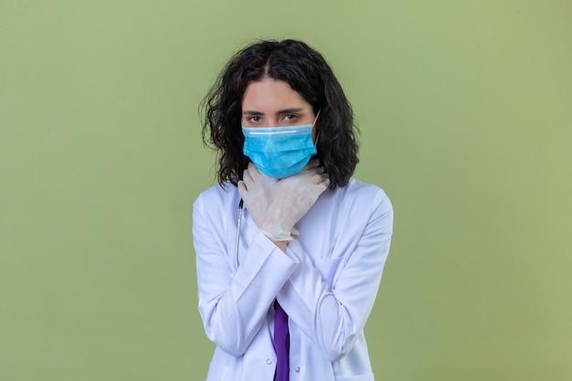 Ärztin, die weißen kittel mit stethoskop in der medizinischen schutzmaske trägt, hält hände auf ihrem nacken wegen halsschmerzen auf isoliertem grün Kostenlose Fotos