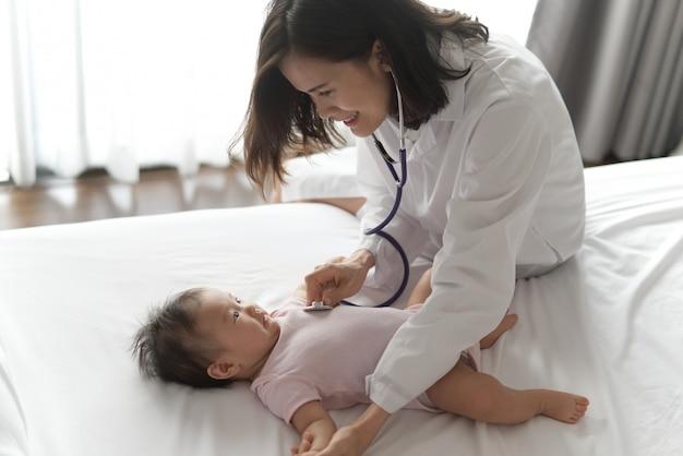 Ärztin hört herzfrequenz des netten neugeborenen babys. Premium Fotos