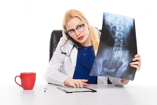 Ärztin im weißen mantel studiert sorgfältig röntgenstrahl Premium Fotos