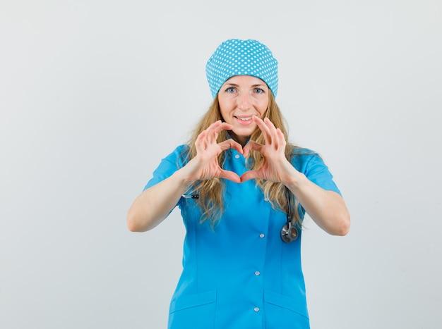 Ärztin in blauer uniform, die herzgeste zeigt und fröhlich schaut Kostenlose Fotos