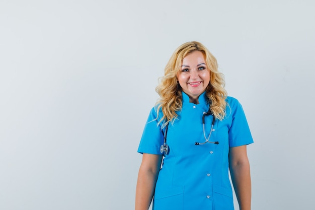 Ärztin in blauer uniform, die lächelt und froh raum für text sucht Kostenlose Fotos