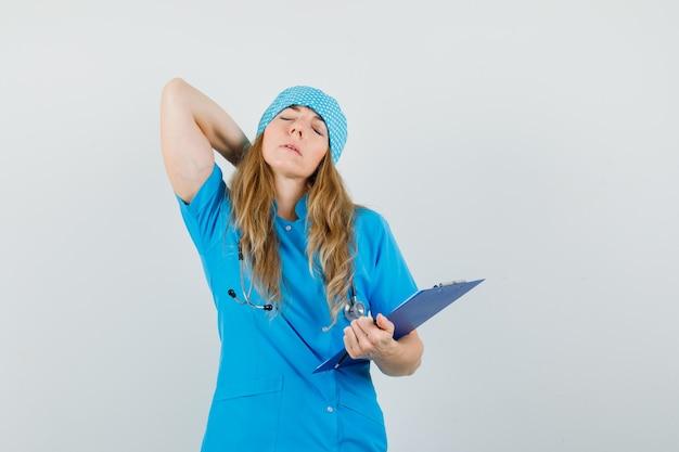 Ärztin in blauer uniform, die unter nackenschmerzen leidet, während sie zwischenablage hält und müde aussieht Kostenlose Fotos