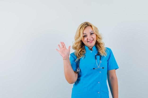 Ärztin in blauer uniform winkt hand zum abschied und sucht zufriedenen raum für text Kostenlose Fotos