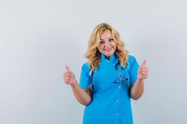 Ärztin in blauer uniform zeigt daumen hoch und sieht froh aus Kostenlose Fotos