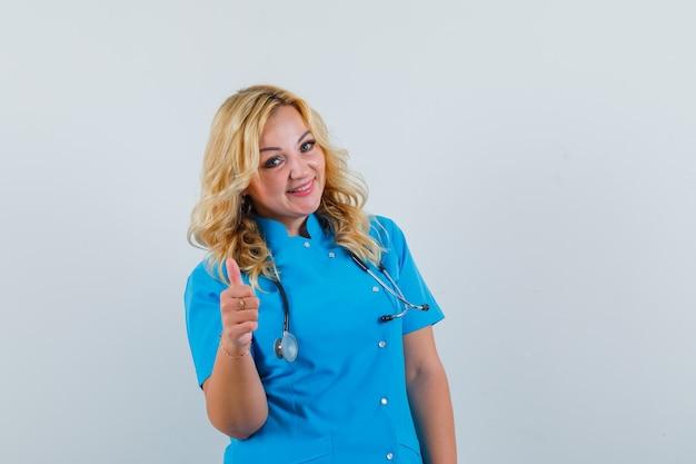 Ärztin in blauer uniform zeigt daumen hoch und sieht glücklich aus Kostenlose Fotos