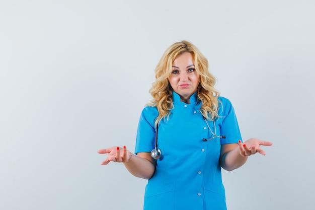 Ärztin in blauer uniform zeigt hilflose geste und sieht ängstlich aus Kostenlose Fotos