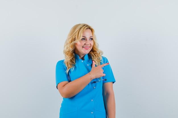 Ärztin in blauer uniform zeigt zur seite und sieht optimistisch aus Kostenlose Fotos