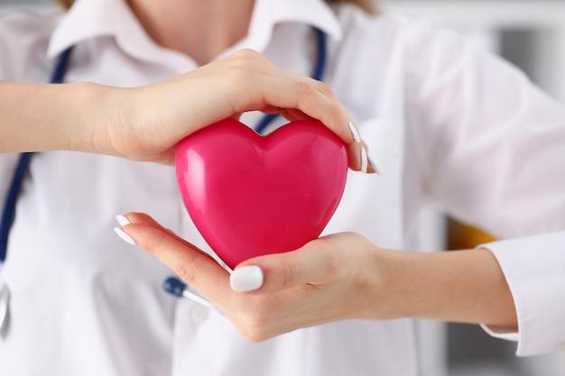 Ärztin in den armen halten und rotes spielzeug abdecken Premium Fotos