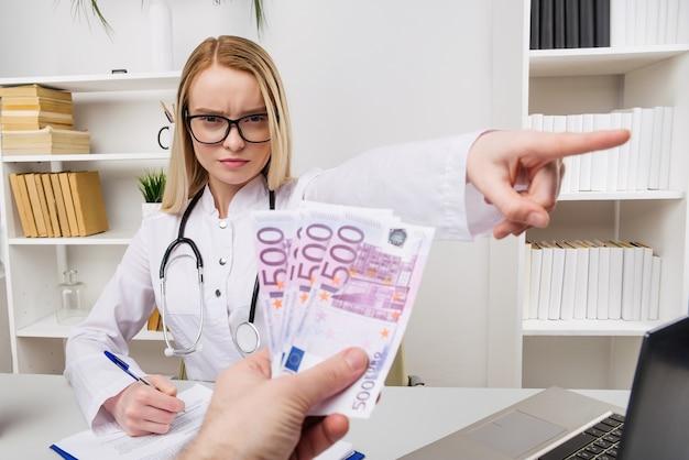 Ärztin mit stethoskop, das bestechungsgelder oder rückschläge ablehnt, währungen euro, patient, der geld für medizinische dienstleistungen gibt, konzept der korruption Premium Fotos