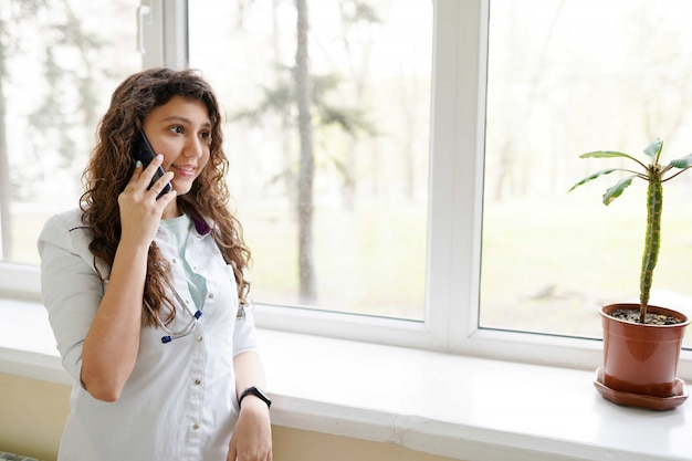 Ärztin mit stethoskop sprechend am handy in der klinik Premium Fotos