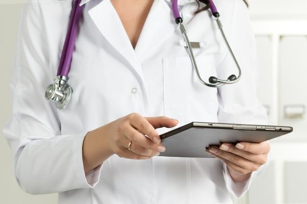 Ärztin mit tablet-pc. die hände des doktors in nahaufnahme. konzept für medizinische versorgung und gesundheitsversorgung. Premium Fotos
