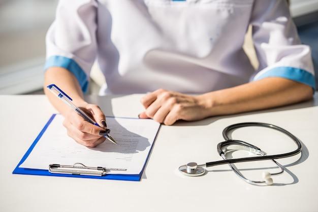 Ärztin sitzt an einem tisch und schreibt. Premium Fotos