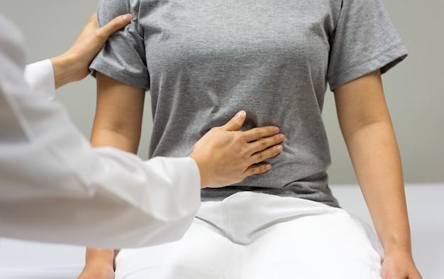 Ärztin überprüfen durch bauchabtastung des weiblichen patienten, der im bett innerhalb der klinik sitzt. Premium Fotos