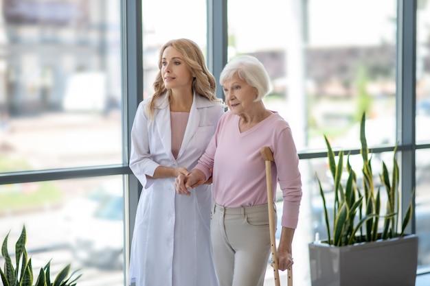 Ärztin und eine ältere frau mit einer krücke, die in einem korridor geht Premium Fotos