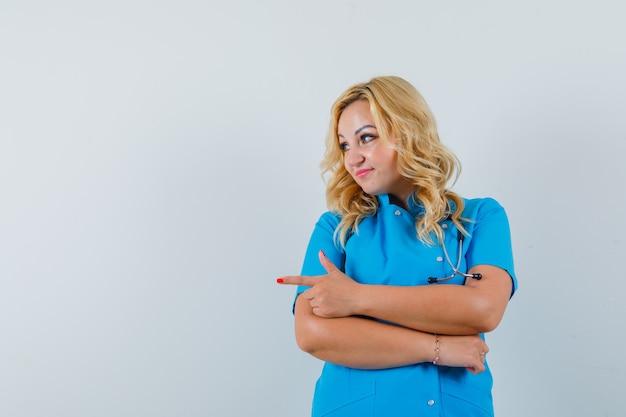 Ärztin zeigt in blauer uniform zur seite und sieht zufrieden aus. platz für text Kostenlose Fotos