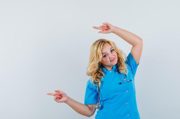 Ärztin zeigt über kopf in blauer uniform und sieht froh aus. platz für text Kostenlose Fotos