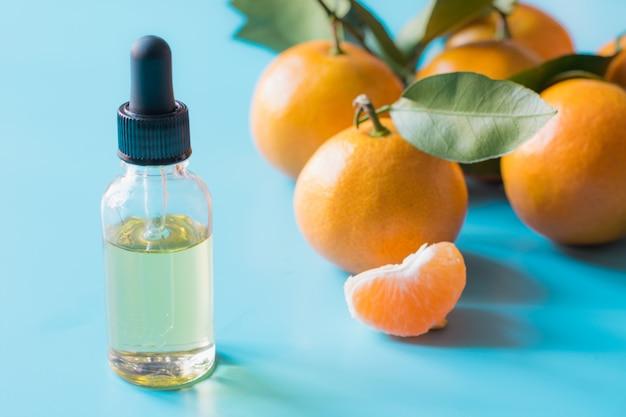 Ätherisches öl der orange mandarine in der glasflasche über blauem pastellhintergrund. hautpflege . Premium Fotos