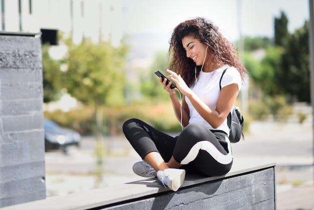 Afrikanerin, die musik mit kopfhörern und intelligentem telefon hört Premium Fotos