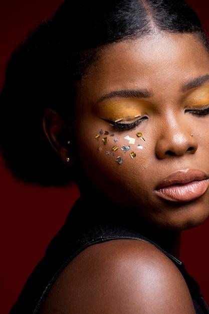 Afrikanische frau in lederweste mit glänzendem konfetti auf den wangen Kostenlose Fotos