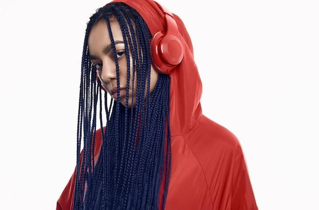 Afrikanische jugendliche mit dreadlocks in hörender musik der roten windjacke Premium Fotos