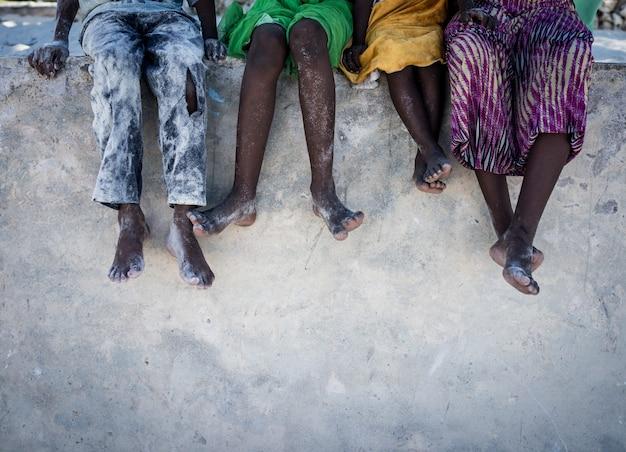 Afrikanische kinder sitzen an der wand mit den füßen nach unten Premium Fotos