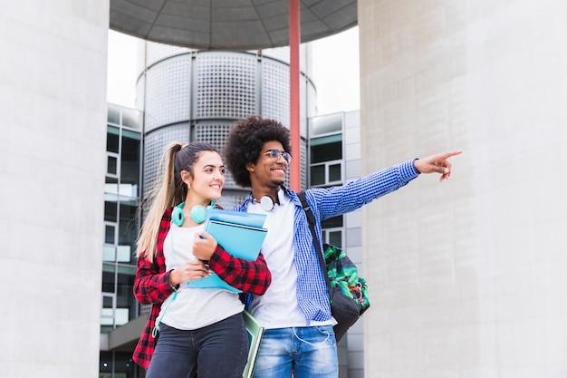 Afrikanische männliche studenten, die außerhalb der universität stehen und seiner freundin etwas zeigen Kostenlose Fotos