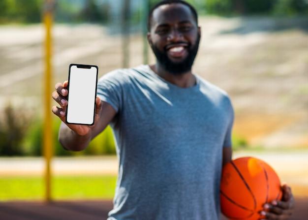 Afrikanischer basketballmann, der sein telefon zeigt Kostenlose Fotos