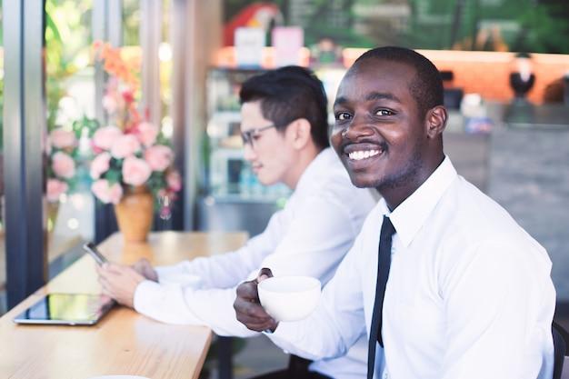 Afrikanischer geschäftsmann, der einen tasse kaffee mit asiatischen freunden hält Premium Fotos