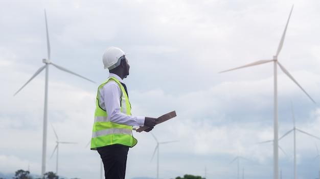 Afrikanischer ingenieur, der mit windkraftanlage steht Premium Fotos