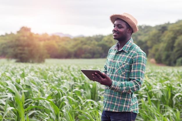 Afrikanischer landwirtstand im grünen bauernhof mit dem halten der tablette Premium Fotos
