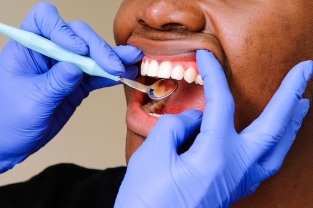 Afrikanischer männlicher patient, der zahnmedizinische behandlung in der zahnmedizinischen klinik erhält Premium Fotos