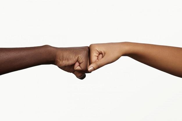 Afrikanischer mann berührt knöchel mit dunkelhäutiger frau als zeichen der übereinstimmung, partnerschaft und zusammenarbeit. Kostenlose Fotos