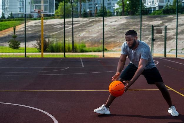 Afrikanischer mann, der ball auf basketballplatz schlägt Kostenlose Fotos