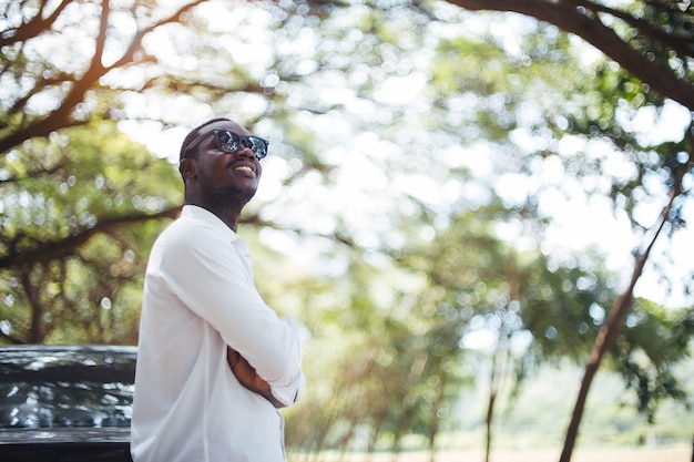Afrikanischer mann, der ein weißes hemd und eine sonnenbrille das auto bereitstehen trägt Premium Fotos