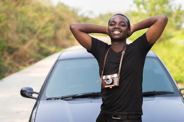 Afrikanischer mann, der eine filmkamera hält und mit einem auto lächelt. Premium Fotos