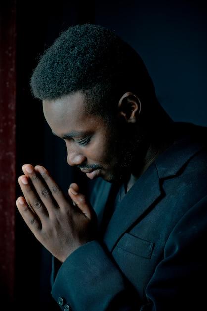 Afrikanischer mann, der für gott im dunklen raum betet. Premium Fotos